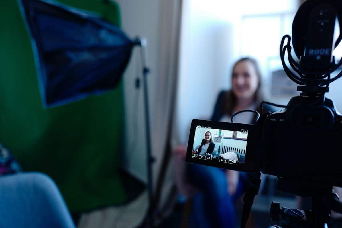 A woman in front of a camera and lights, recording her vlog.