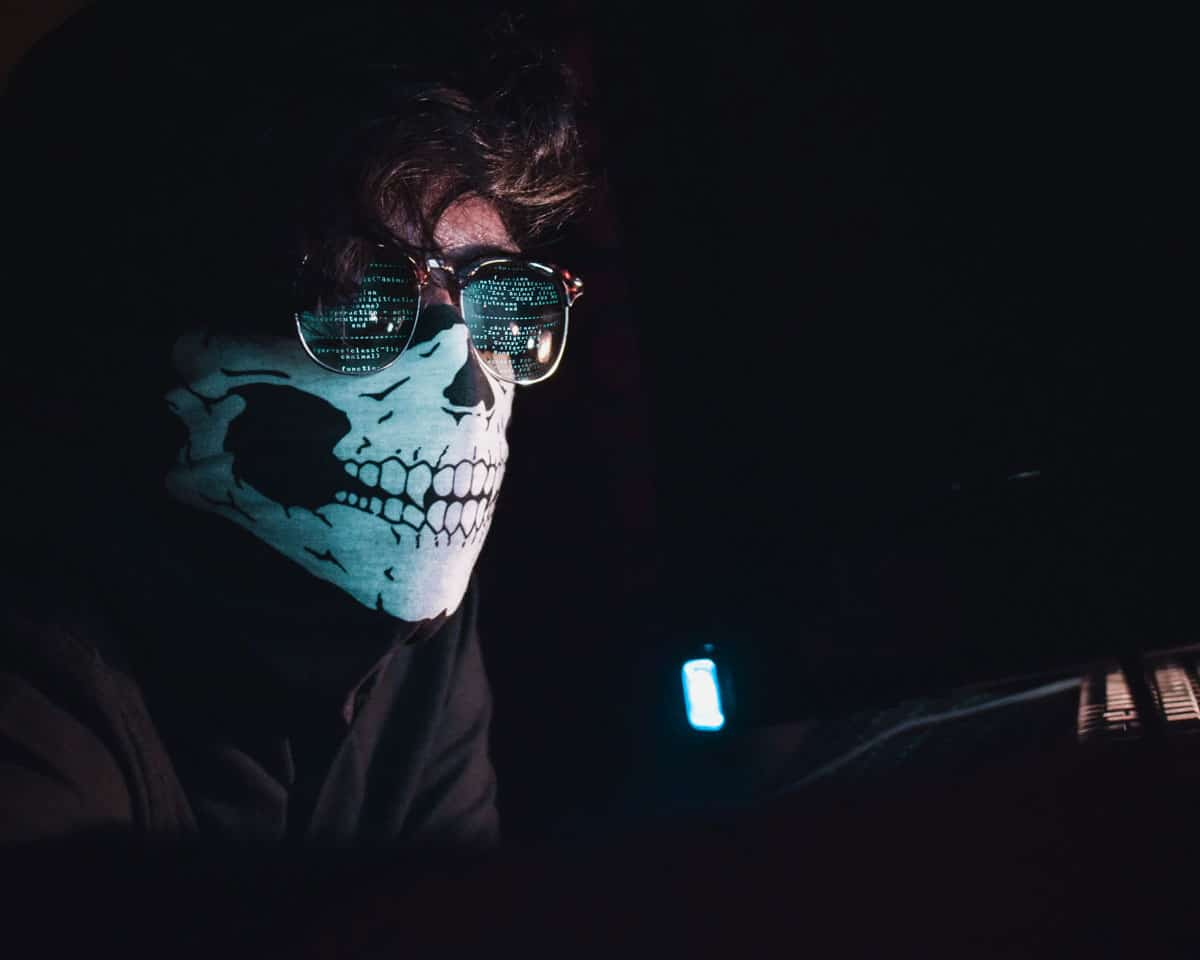 A computer hacker with a skull face mask, reading computer code