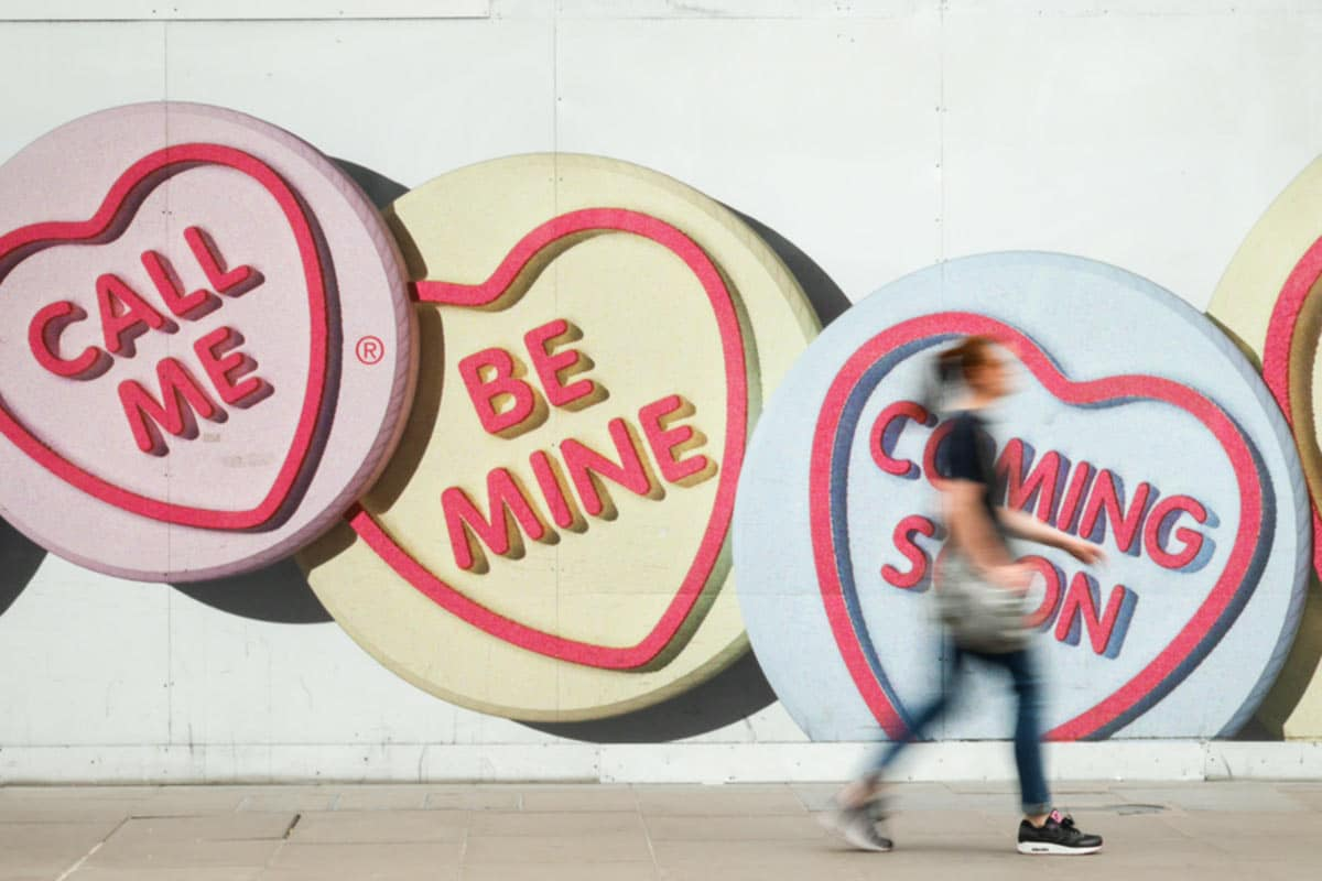 Woman walking in front of candy hearts painted on a wall.