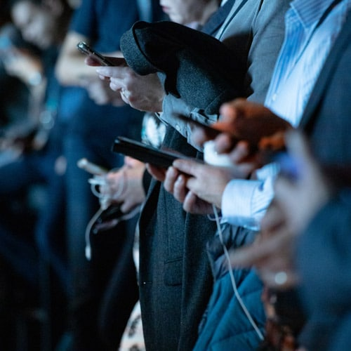 Businesspeople looking at their smartphones during an event.