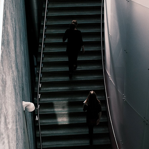 Two women climbing a set of stairs at the Art Gallery of Alberta
